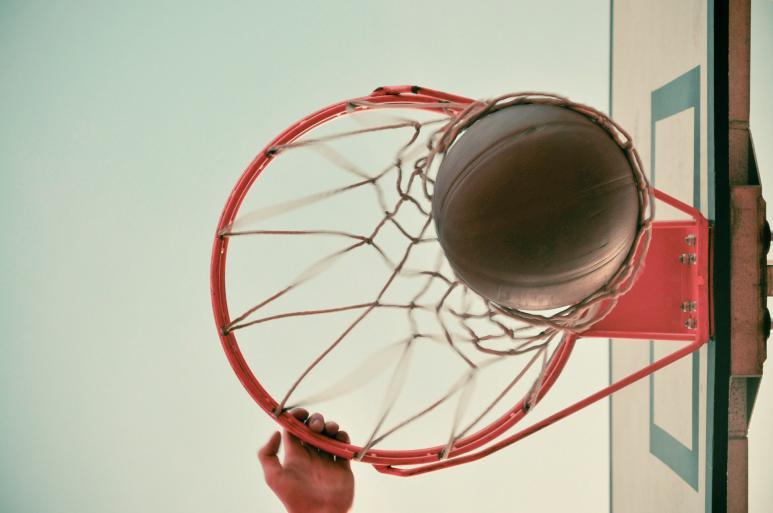 Ein Basketball Korb von unten, ein Ball fällt durch